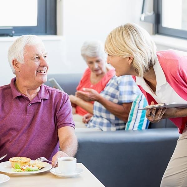 Senior Center employee checking on seniors eating