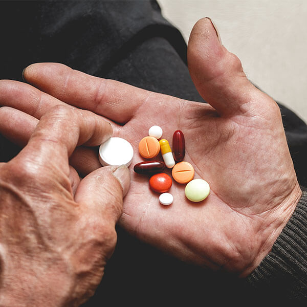 Older adult with handful of pills