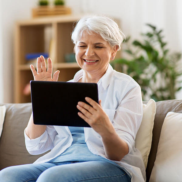Senior woman waving on a video chat