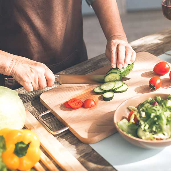Man chopping cucumbers and other vegetables