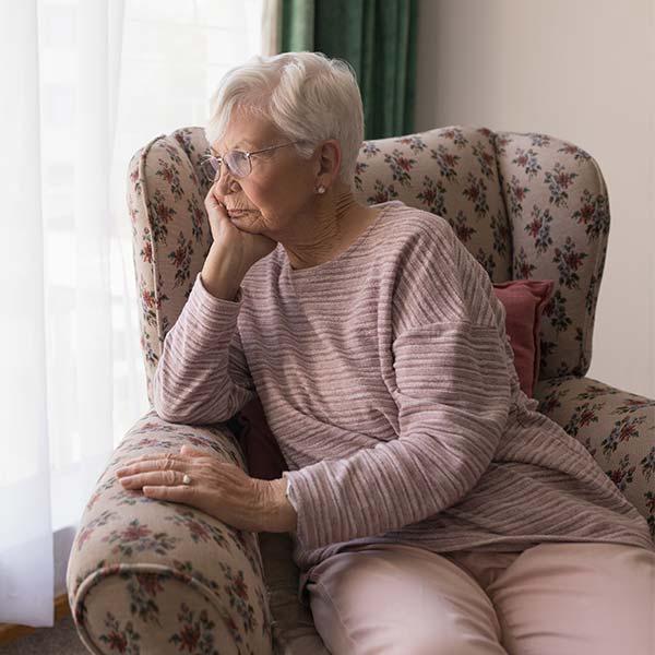 Sad senior citizen looking out window