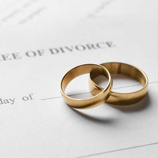 Gold wedding bands on top of divorce paperwork