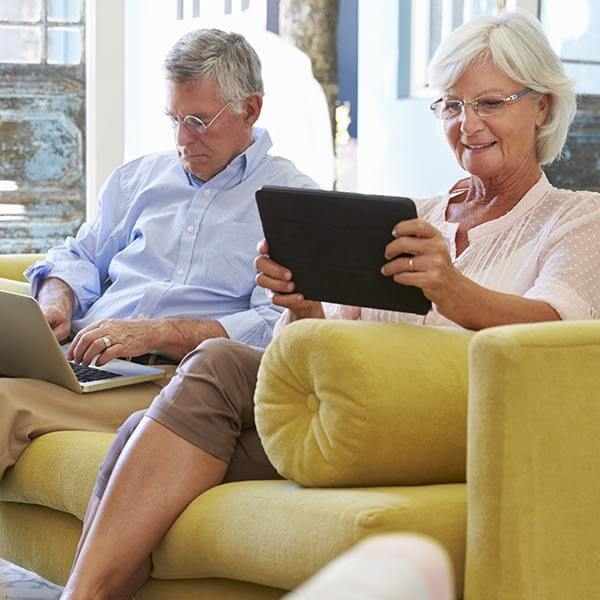 Senior couple each on tablet and computer