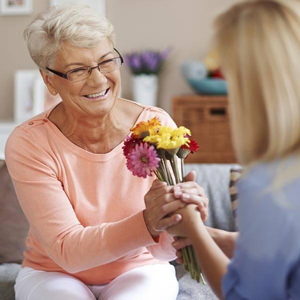 Elderly woman gifting flowers