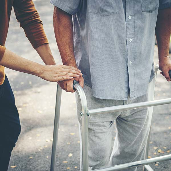 Person assisting their father in a walker