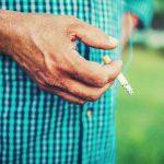 Older man holding lit cigarette