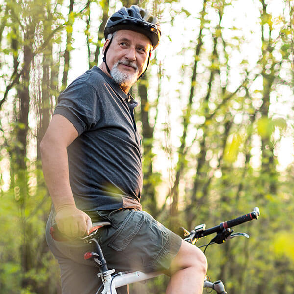 Senior man riding bike on wooded trail