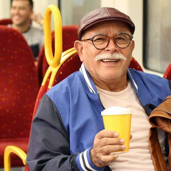 Senior man riding bus with coffee
