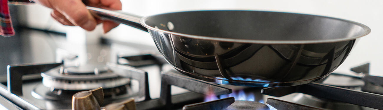 Person cooking over gas stove